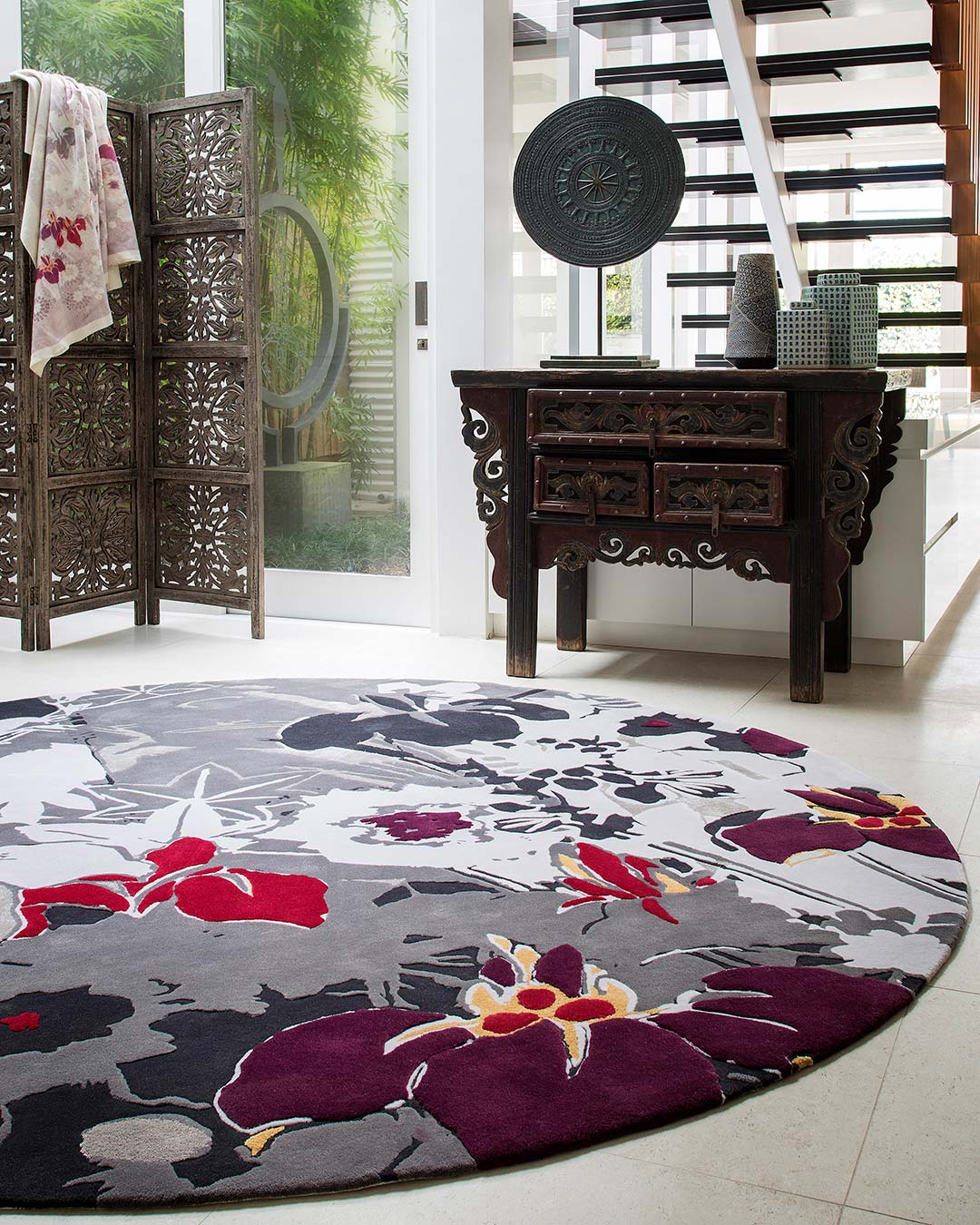 location bedroom shot of ayame round rug by akira floral pattern in grey purple and red