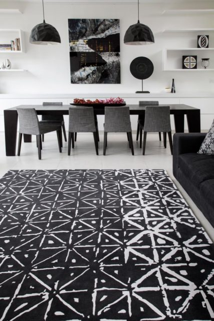location living room shot of batik rug by akira with a black background and white dots and dashes pattern