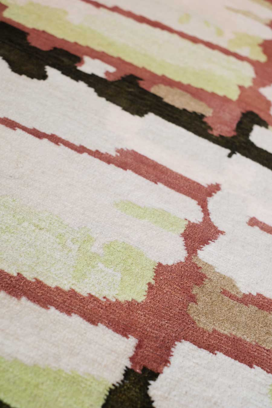 Close up of fence rug by anna carin in abstract mirrored pattern beige background