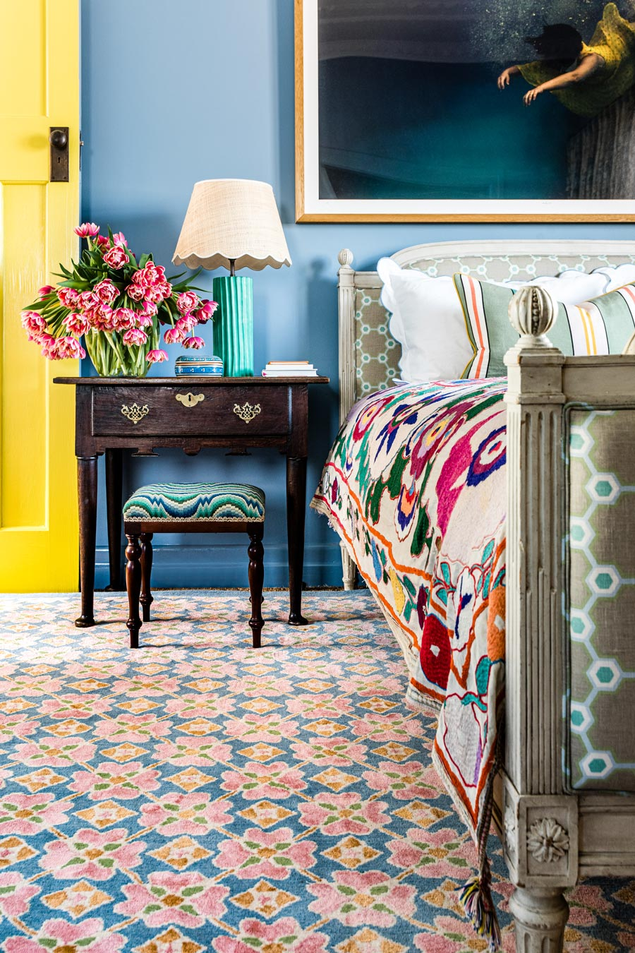 location bedroom shot of flora rug by anna spiro in floral repeat pattern with a blue border