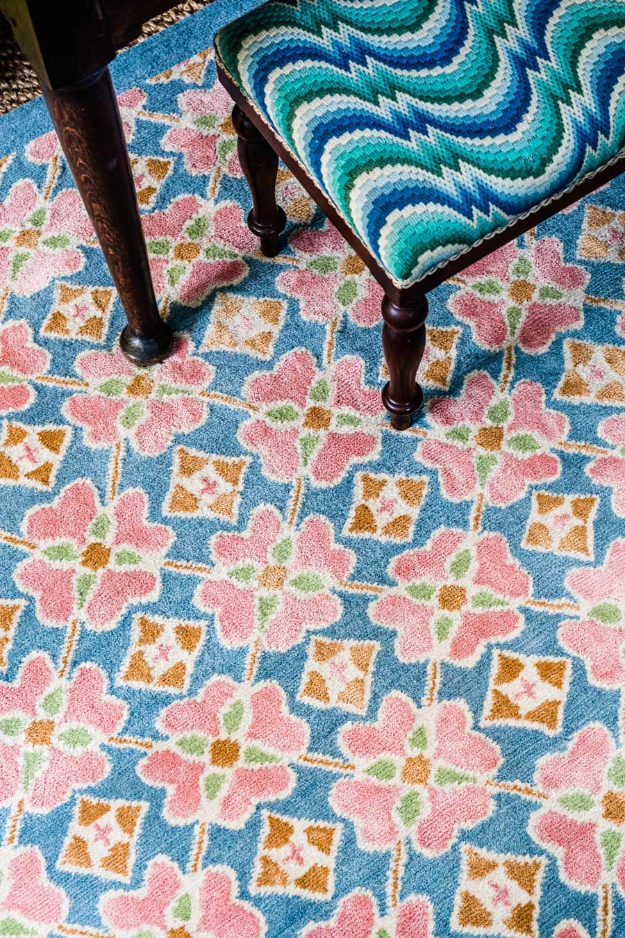 close up of flora rug by anna spiro in floral repeat pattern with a blue border