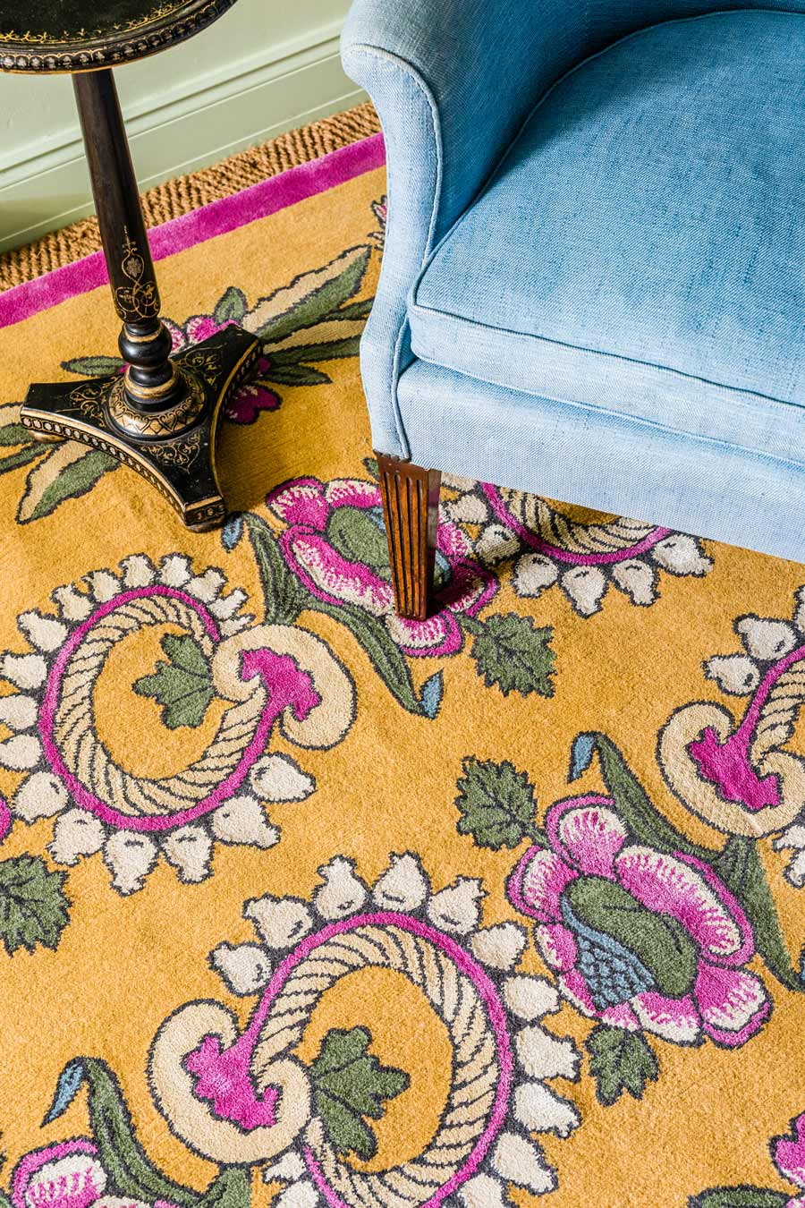 close up of kandilli rug by anna spiro in abstract floral pattern mustard background and pink border