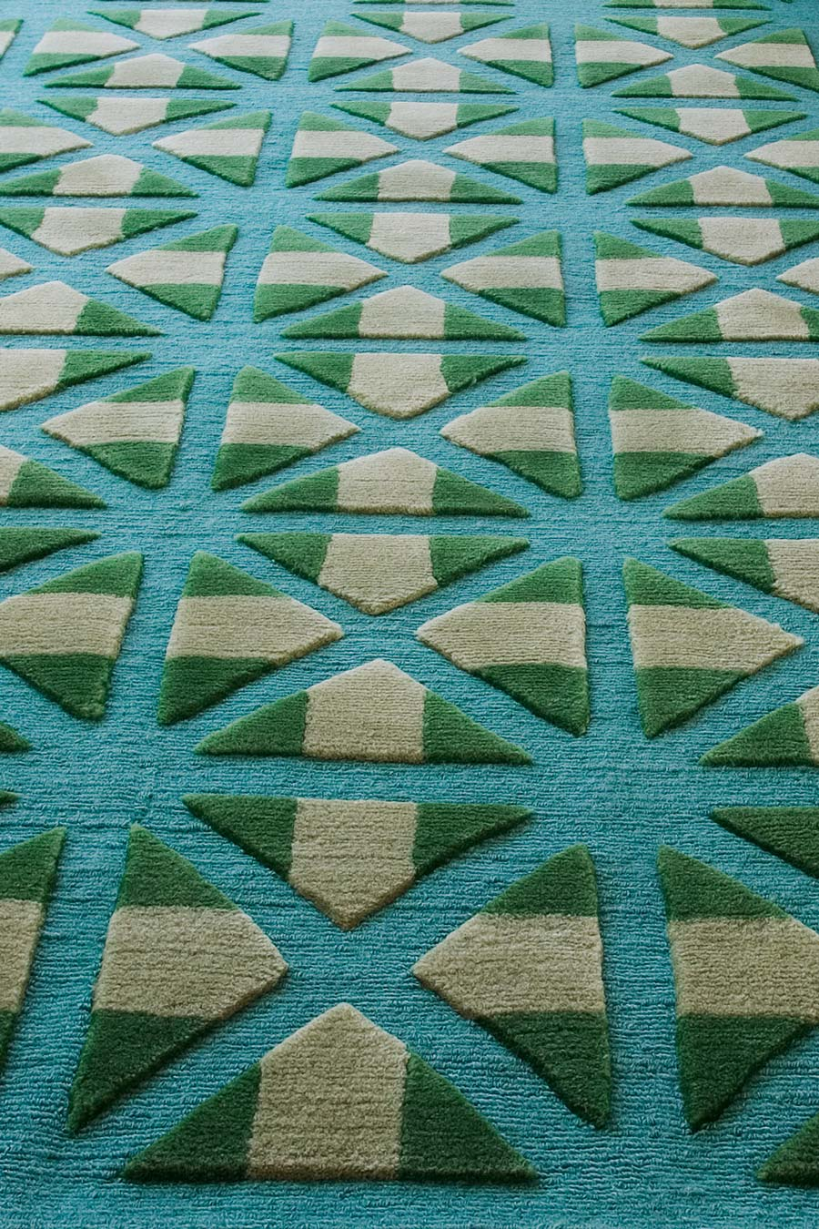 close up of bias rug by bernabeifreeman in blue and green repeat geometric pattern