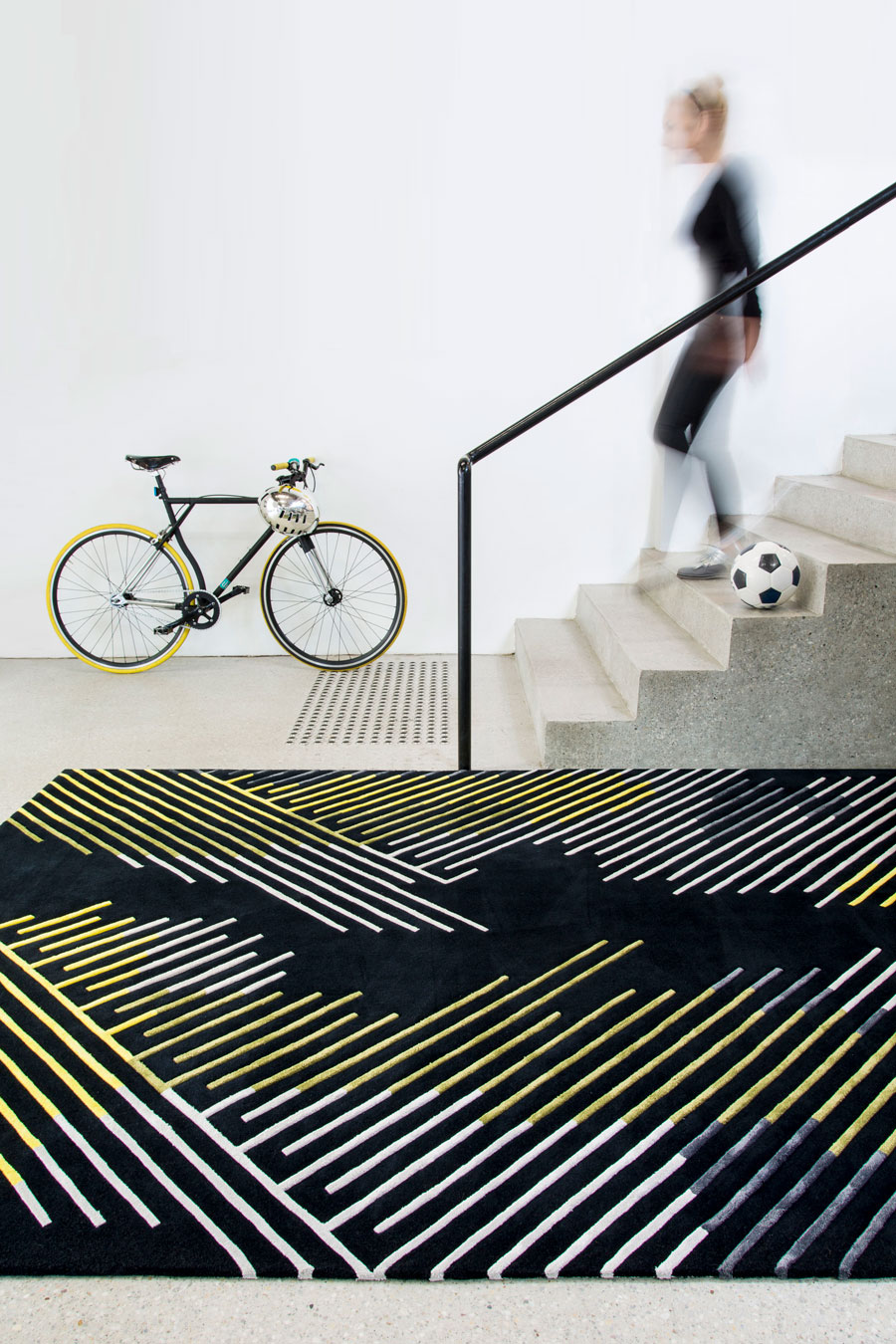 location shot of minotu rug by bleux in multi linear pattern black background