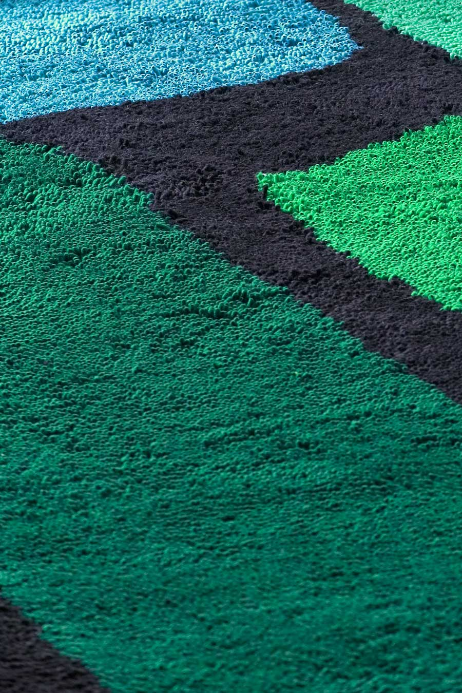 close up of jewel rug by dinosaur designs green and blue large shapes on black background