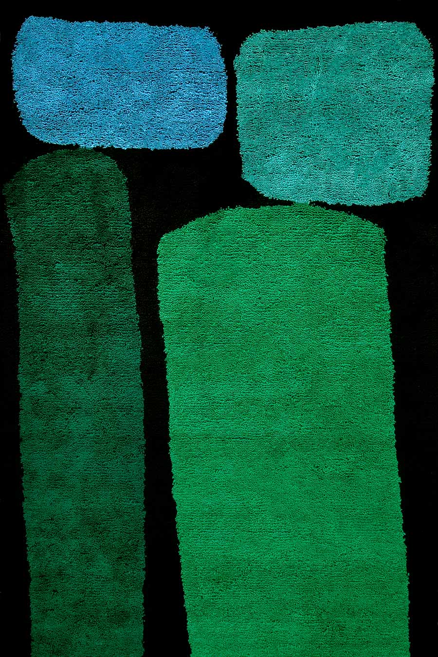 overhead of jewel rug by dinosaur designs green and blue large shapes on black background