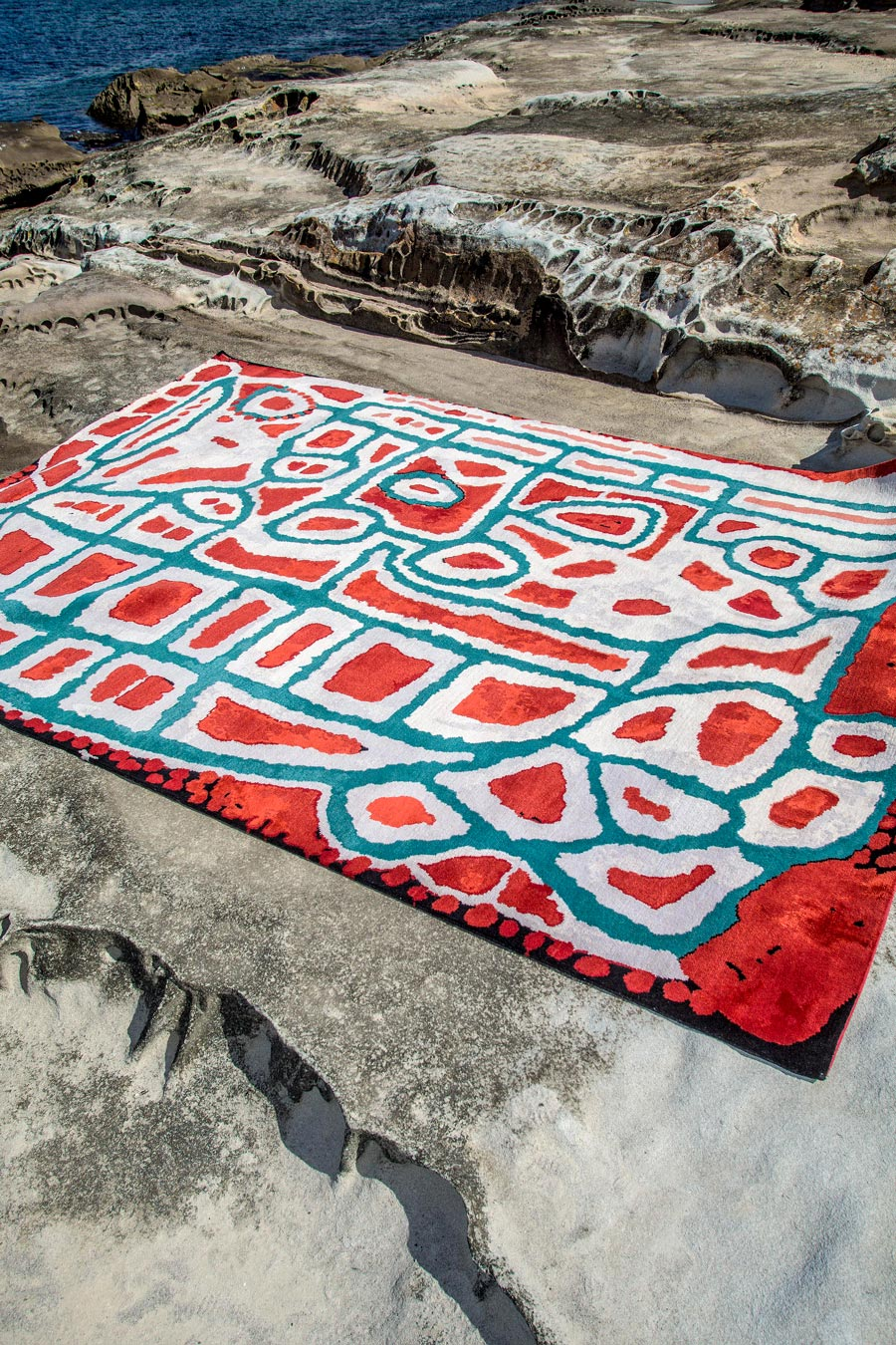 Indigenous Lungarung rug in red and green colour in a coastal setting