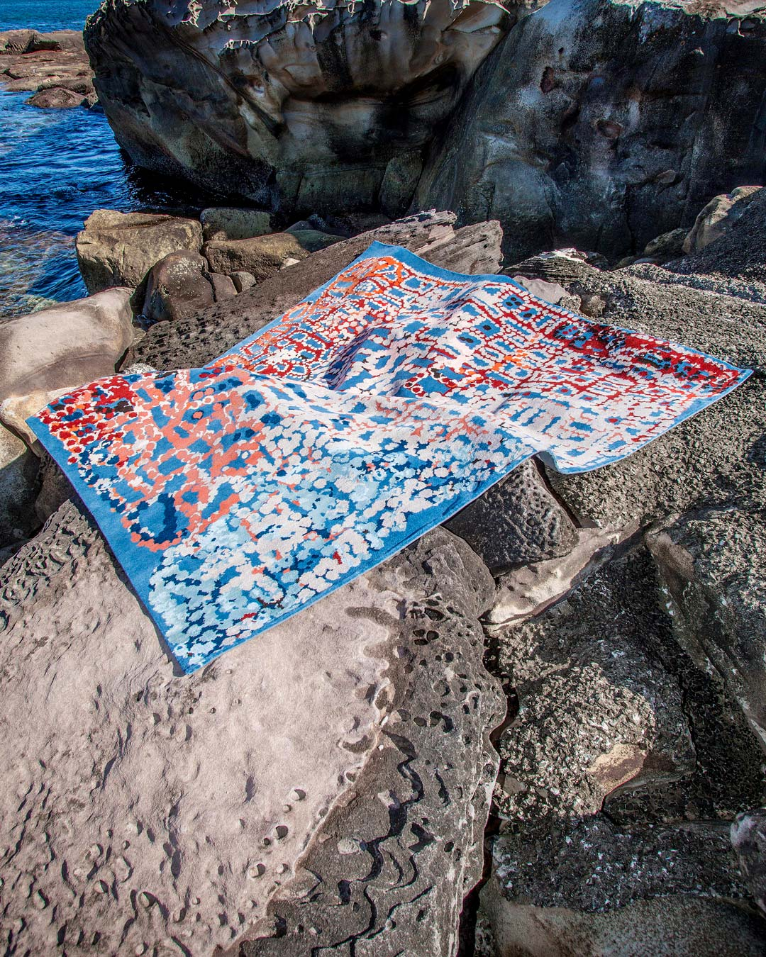 Indigenous Pinkalarta rug in pink and blue colour laid on rocks