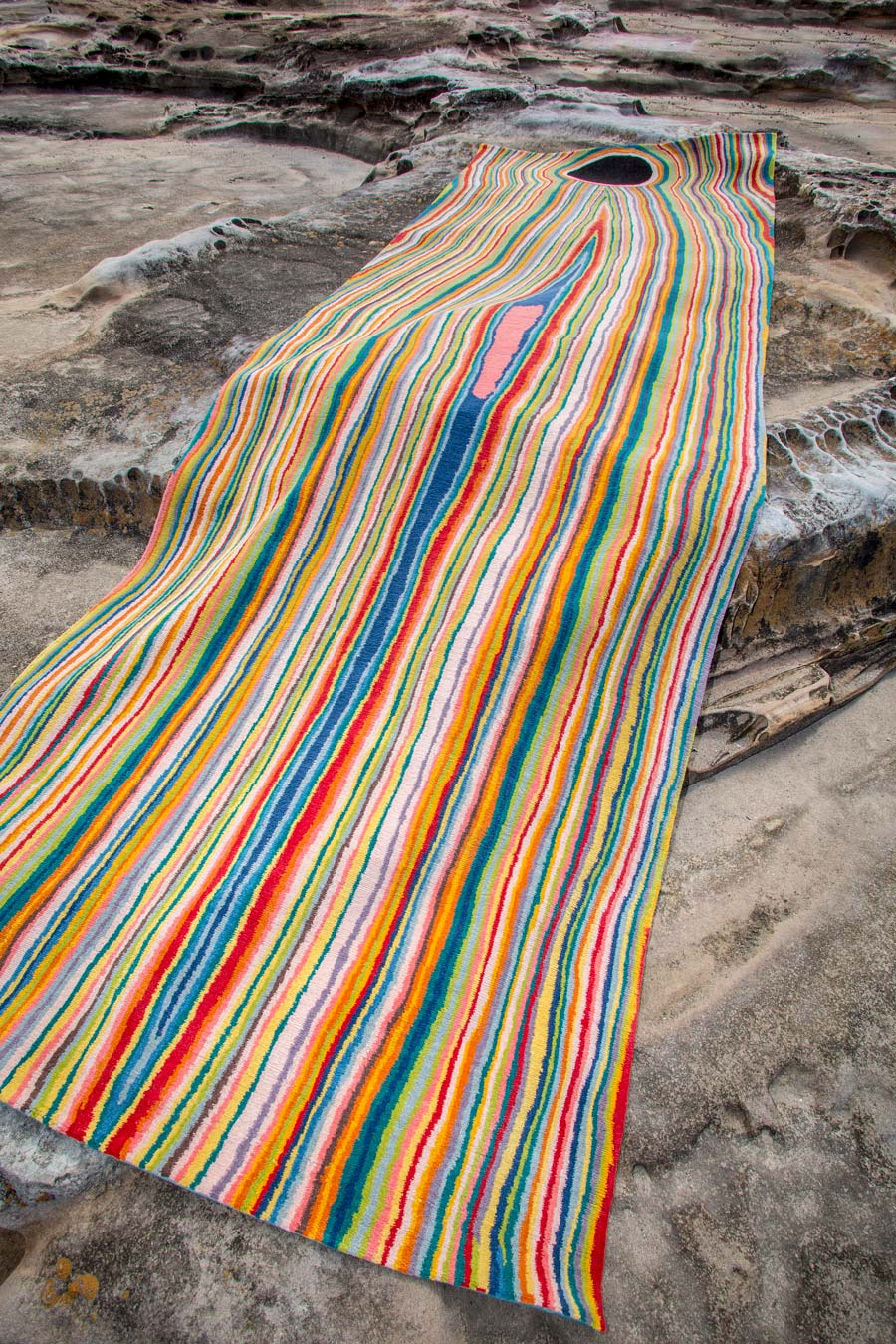 Overhead view of indigenous Untitled 2006 rug in rainbow colours