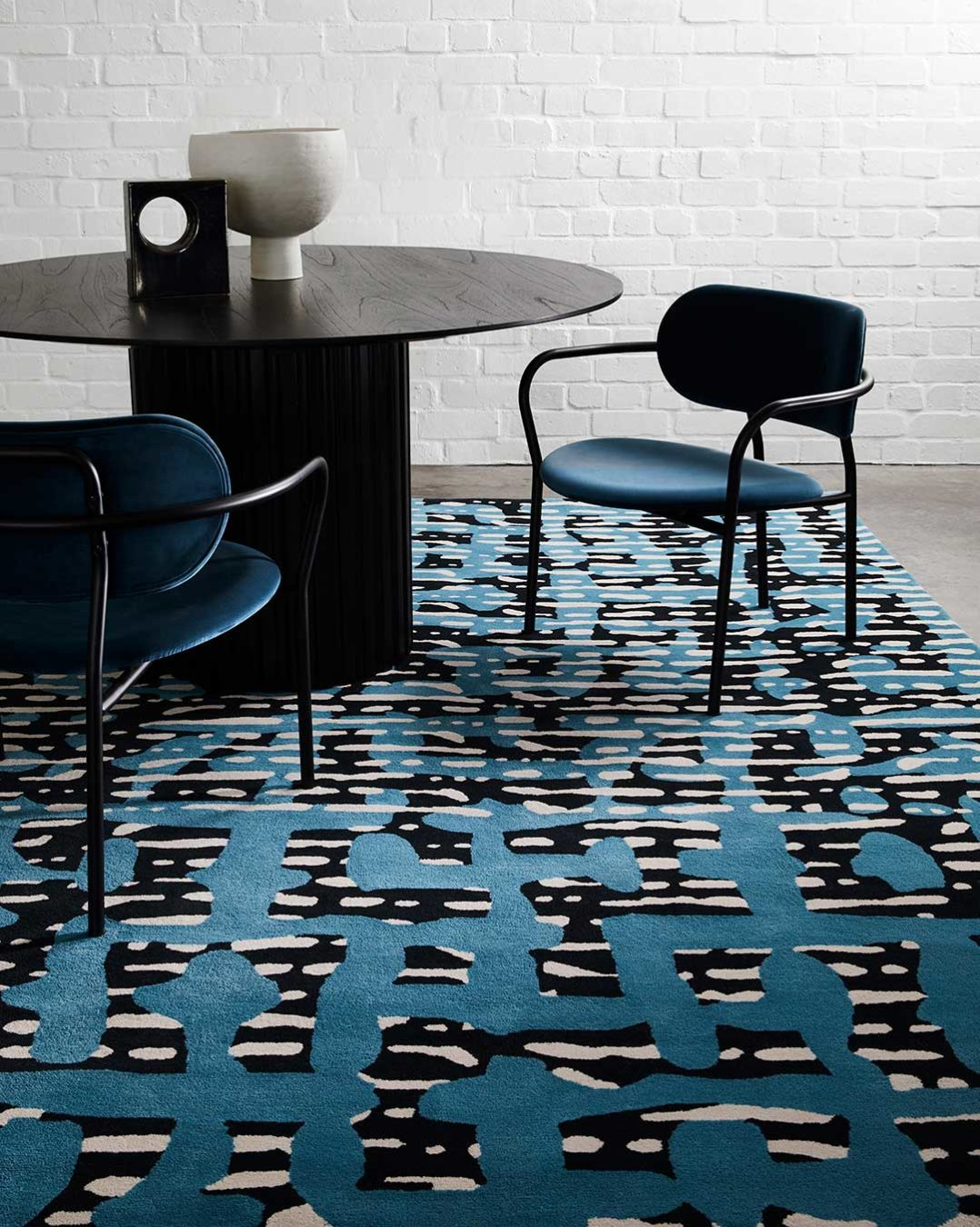 Dining room view of modern, striped Evie rug in blue and navy.