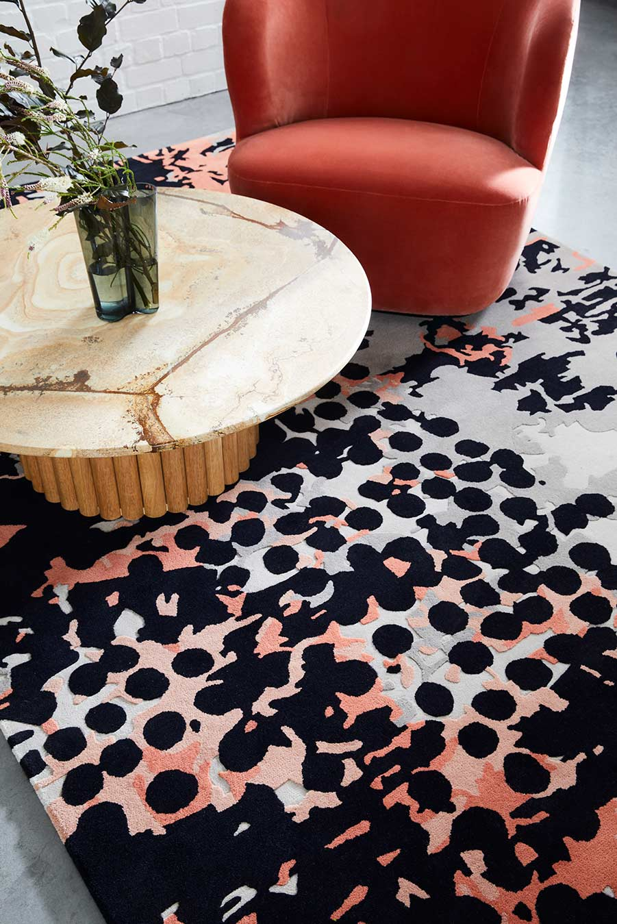 Living room view of modern, spotted Franco rug in Light grey, charcoal, pink and red.