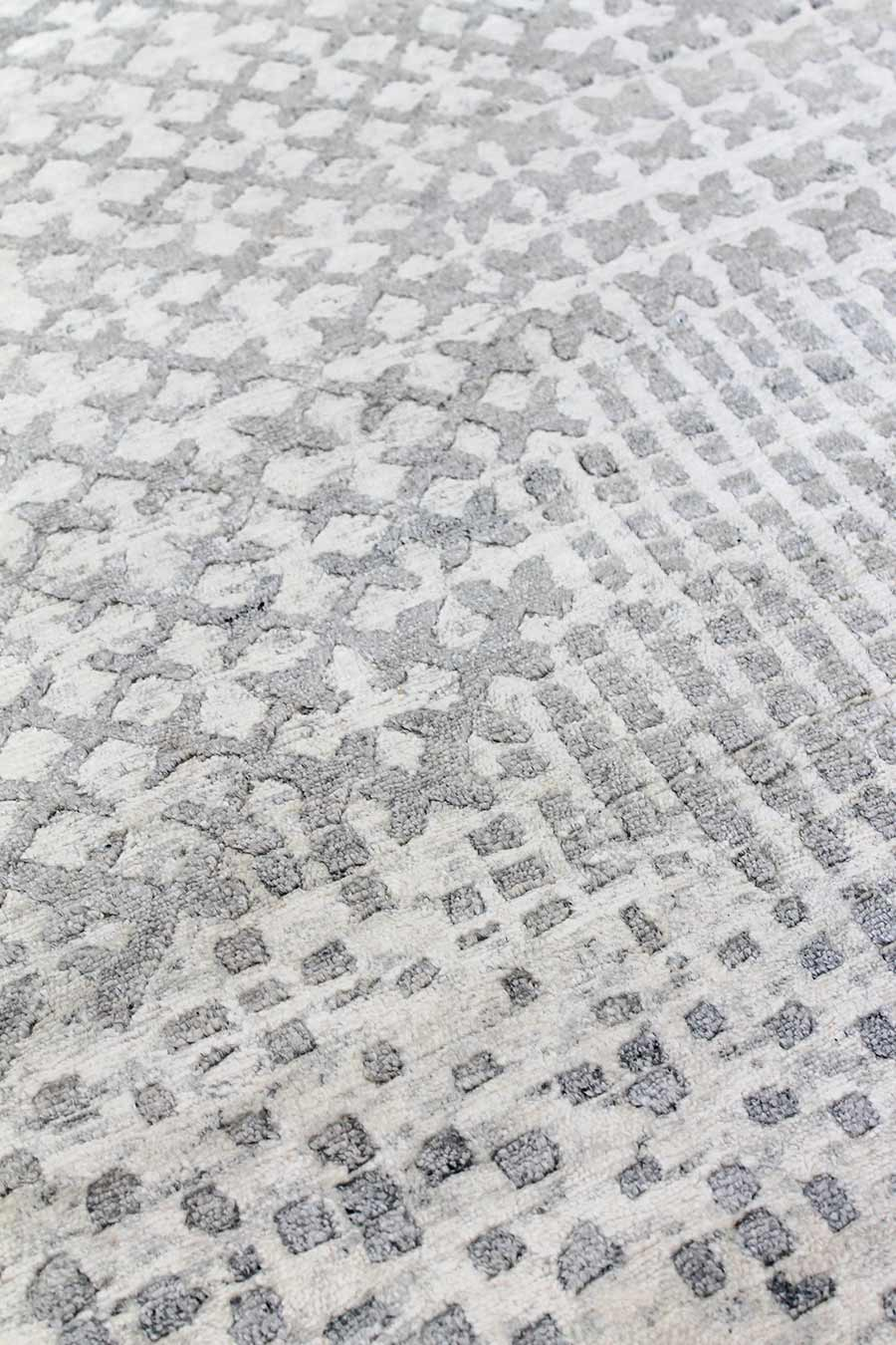 Close up image of patterned Moulin handknot rug in silver colour
