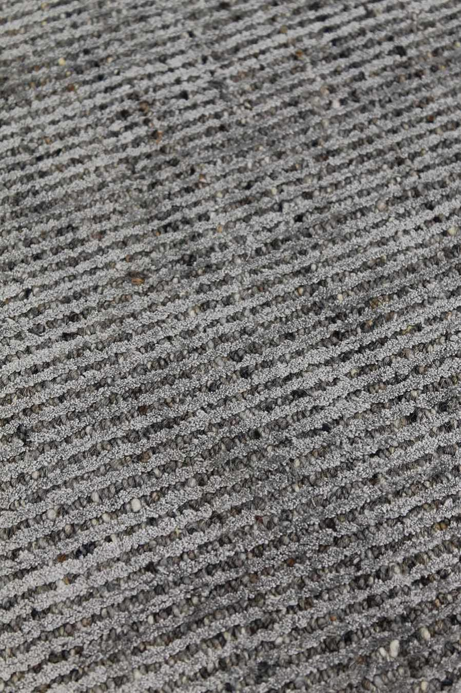 Detailed image of textured Gomez rug in dark grey colour