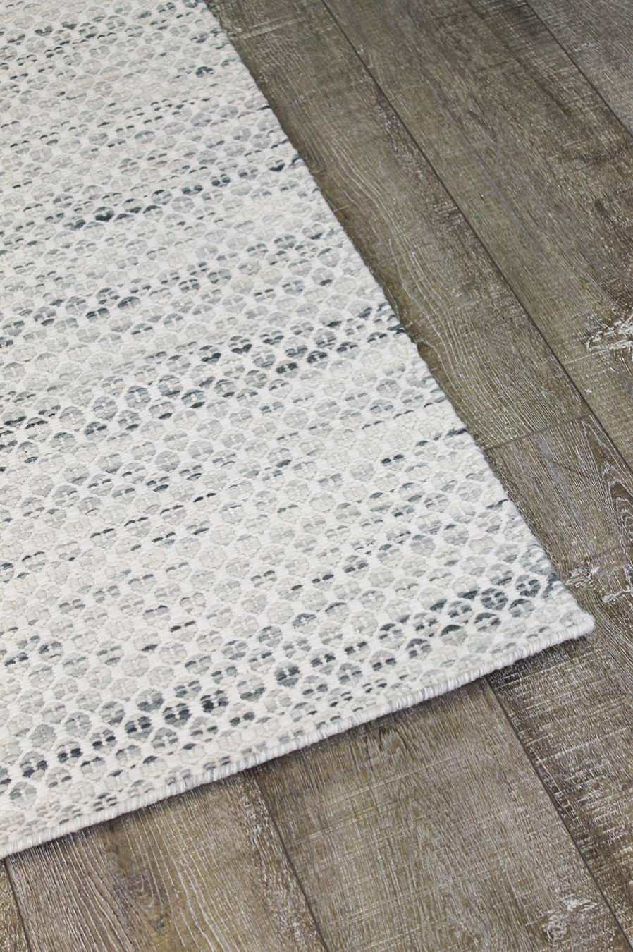 Detailed image of textured Plait Hive rug in ivory colour