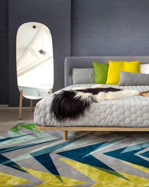 Bedroom view of our gemoetrically patterned Anika rug in navy, yellow and blue
