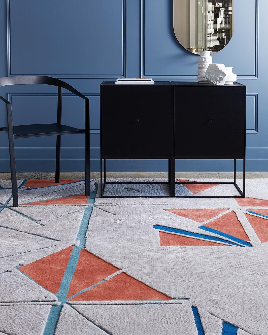 Styled setting of the geometric and modern Despatch rug design in orange and teal